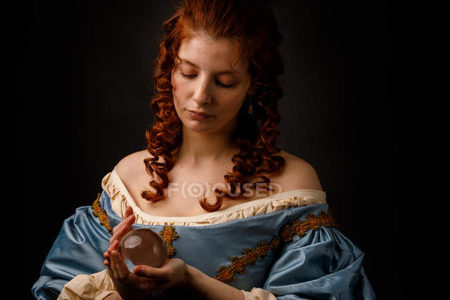 Baroque woman looking down while holding magical glass ball. — Stock Photo