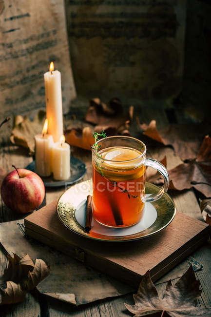 Cup of fresh tea with lemon placed near ripe apple and flaming candles amidst autumn leaves. — Stock Photo