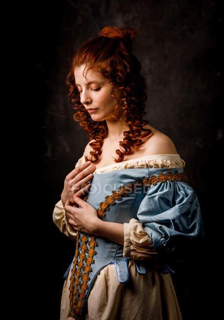 Красивая женщина в средневековой одежде позирует на черном фоне . — стоковое фото