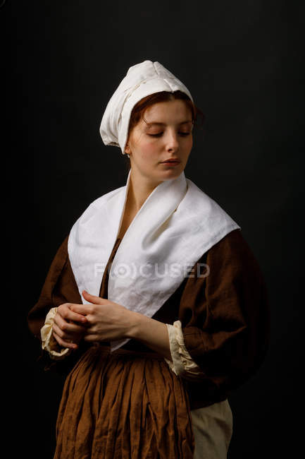 Pretty female in simple medieval clothing with eyes closed on black background. — Stockfoto