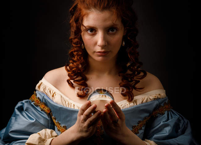 Lovely woman in elegant medieval dress holding glass ball and looking in camera. — Stock Photo
