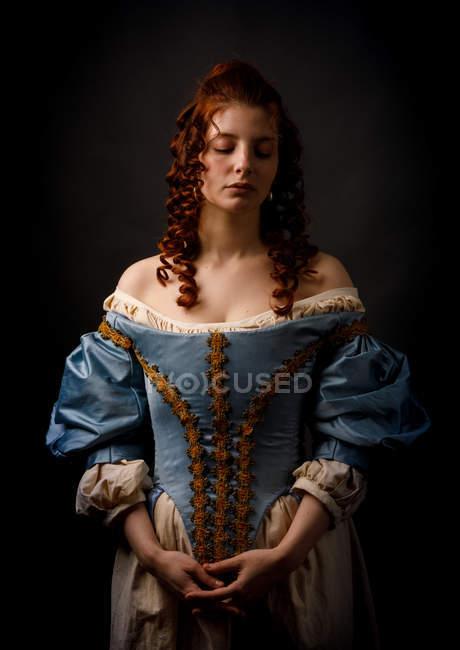 Schöne Frau in mittelalterlicher Kleidung auf schwarzem Hintergrund. — Stockfoto