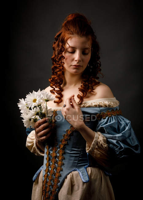 Pretty woman in medieval dress with eyes closed holding bunch of white flowers. — Stock Photo