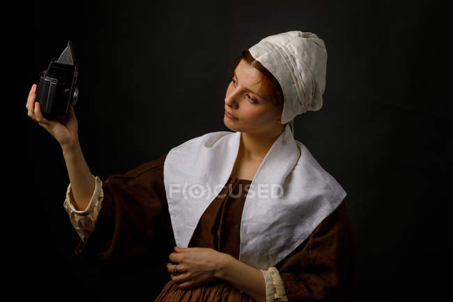 Beautiful female in simple medieval dress using old photo camera for selfie. — стокове фото