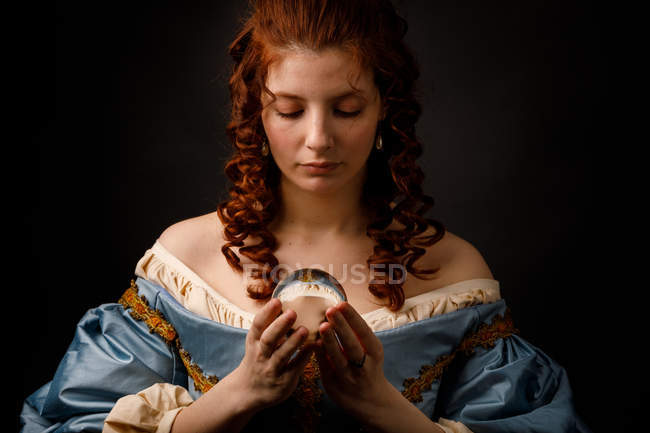 Pretty woman in vintage Victorian dress looking down while holding magical glass ball. — Stock Photo