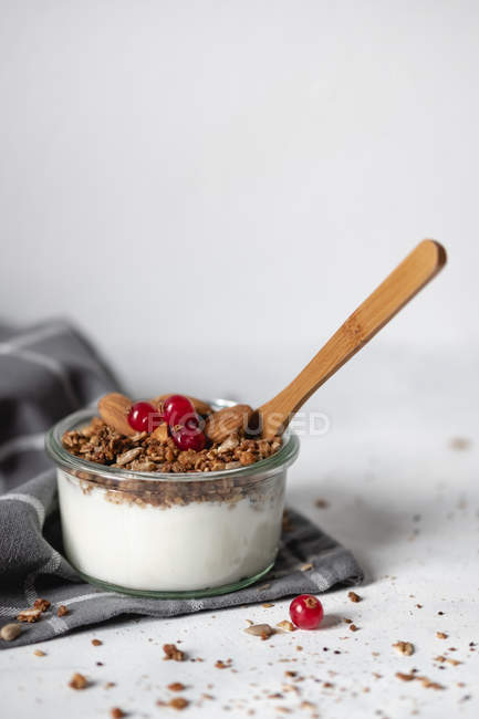 Bowl of fresh healthy yogurt with cereals and cranberries  on gray napkin — Stock Photo
