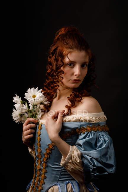 Чудова жінка у середньовічному одязі, яка тримає стокротки і дивиться в камеру.. — стокове фото