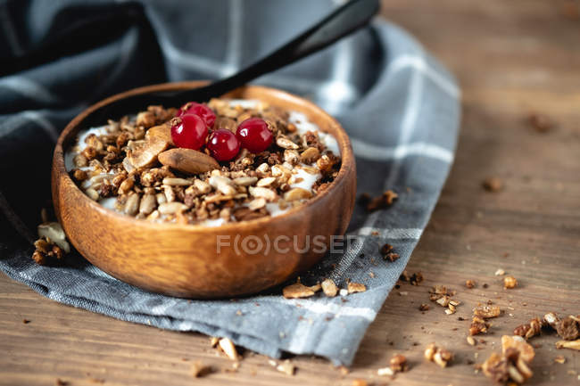Yogurt with cereals and cranberries in wooden bowl on fabric — стокове фото