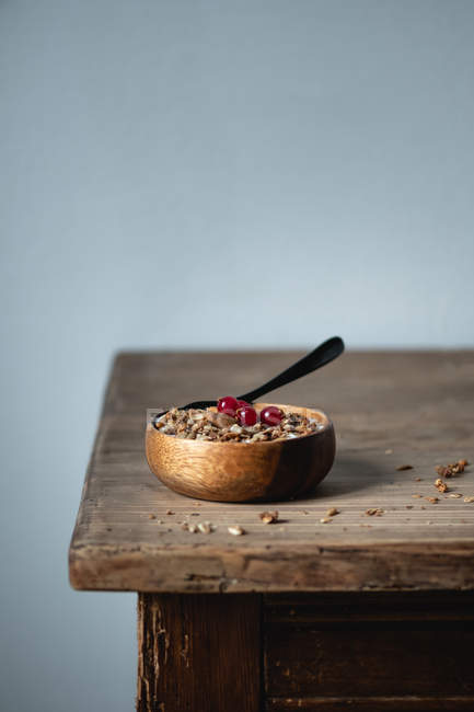 Yogurt with cereals and cranberries in wooden bowl on rustic table — Stock Photo