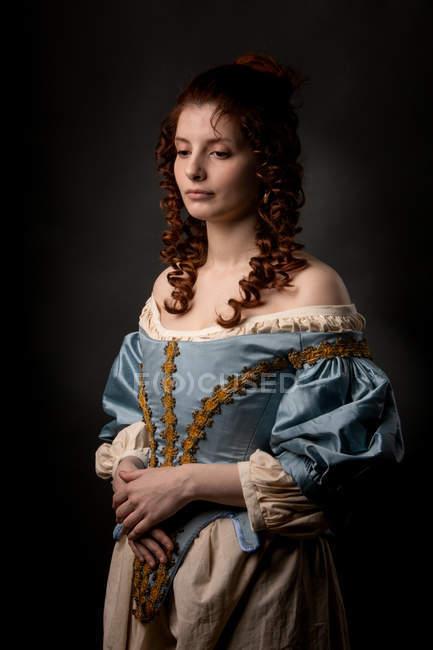 Привлекательная юная леди в красивом платье в стиле барокко с руками на животе на черном фоне . — стоковое фото