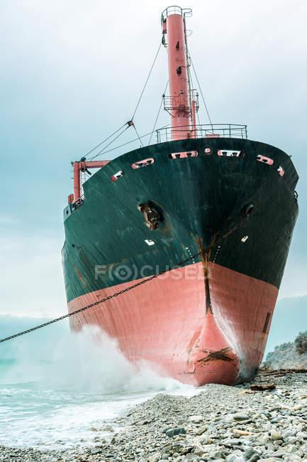 Vaste navire de métal situé près de la côte contre un ciel bleu nuageux. — Photo de stock