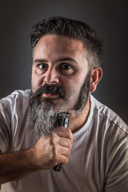 Barber shaving beard and looking at camera — Stock Photo