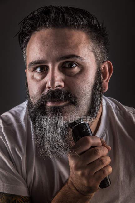 Hombre adulto guapo que usa rasguño eléctrico para afeitarse la barba y mirar la cámara mientras está de pie sobre fondo gris. - foto de stock