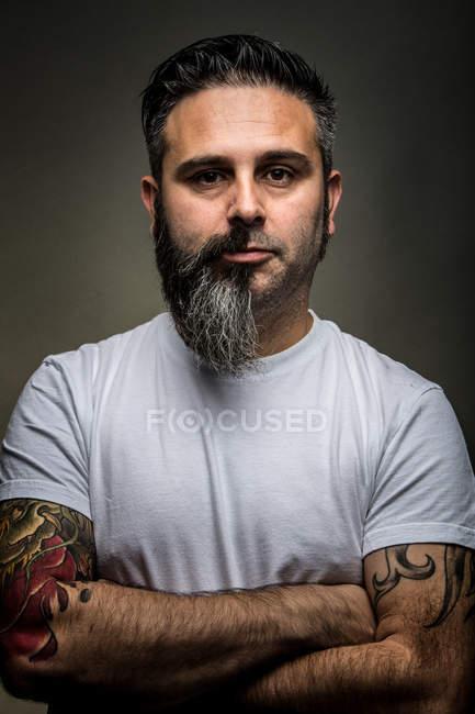 Un guapo adulto con media barba cruzando los brazos y mirando a la cámara mientras se encuentra en un fondo gris. - foto de stock