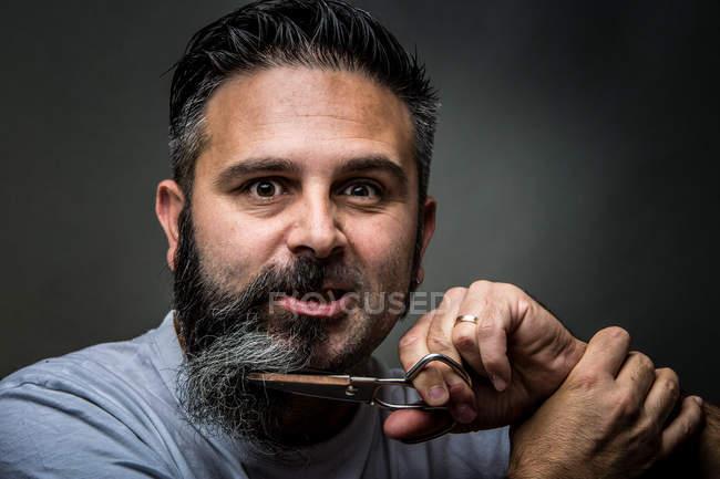 Barberes expresivos que cortan barbas - foto de stock
