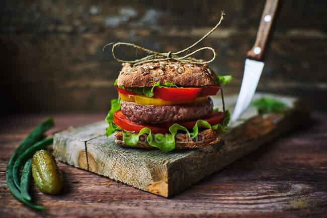 Sabrosa hamburguesa fresca atada con hilo de lino acostado sobre tabla de madera aserrada - foto de stock