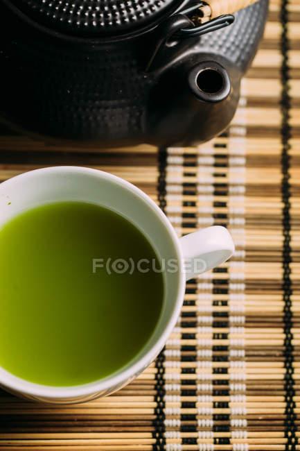 Nahaufnahme der Tasse mit frischem grünen Matcha-Tee und Vintage-Kanne auf dem Tisch. — Stockfoto