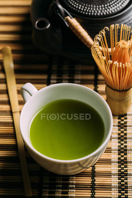 Close-up of cup with fresh green matcha tea, vintage pot and bamboo whisk preparing tool on table. — Stock Photo