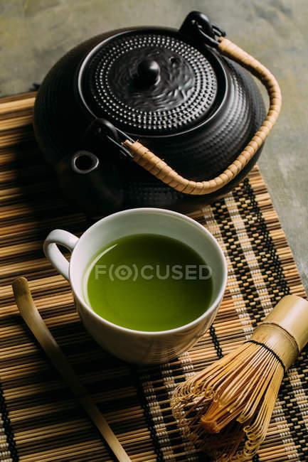 Крупный план чашки со свежим зеленым чаем маття, винтажным горшком и бамбуковым венчиком на столе . — стоковое фото