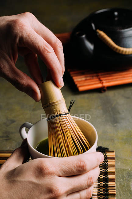 Close-up of hands of person preparing matcha tea with bamboo whisk. — Stock Photo
