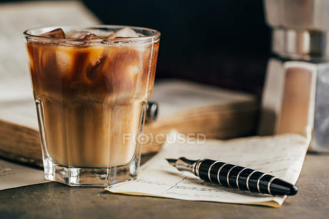 Cold espresso coffee in glass glass on dark grunge background with old book — Stock Photo