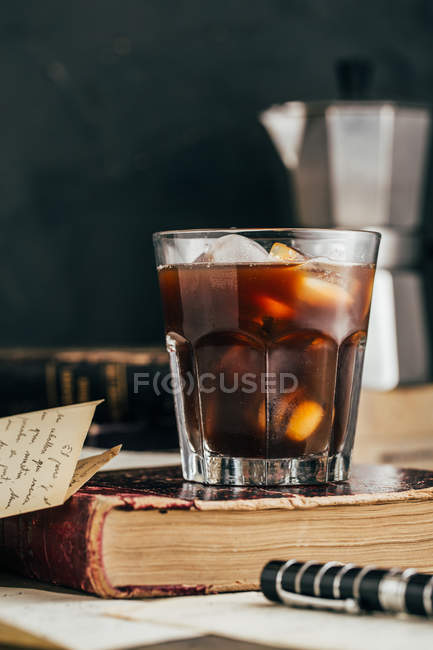 Cold espresso coffee in glass on dark grunge background with antique book — Stock Photo