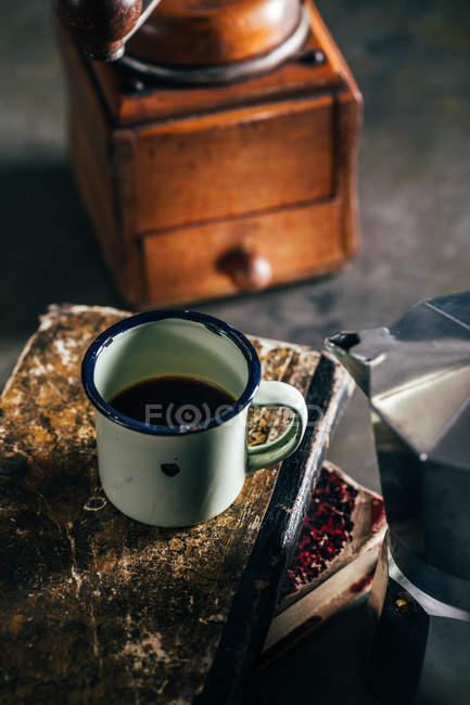 Горячий кофе в чашке эмали на старых потрепанных книгах — стоковое фото