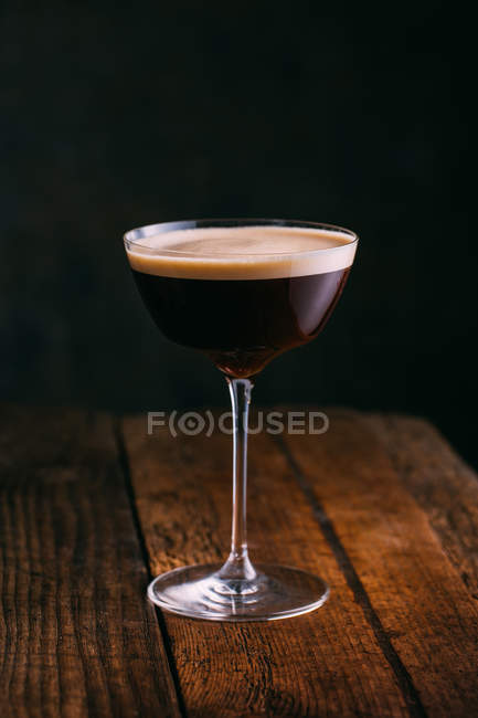 Espresso martini cocktail served in glass on wooden table — Stock Photo