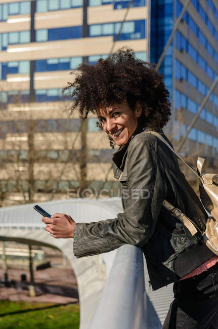 Woman with afro hair looking at her phone while walking on a bridge in a city — Stock Photo