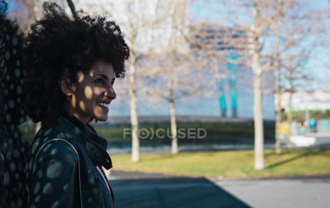 Retrato de mujer negra con el pelo afro apoyado en una pared en la calle - foto de stock