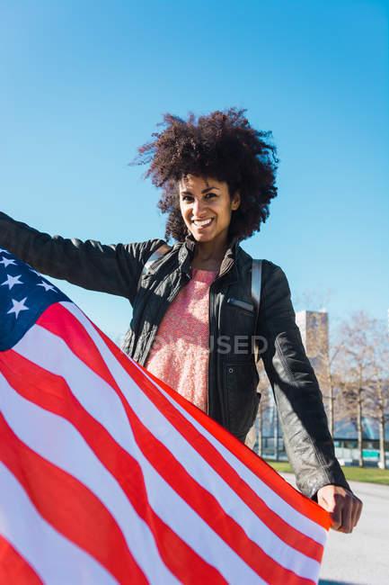 Черная женщина с афроволосами и американским флагом, празднующим День независимости США — стоковое фото
