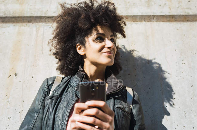 Portrait of black woman with afro hair leaning on a wall in the street — Stock Photo