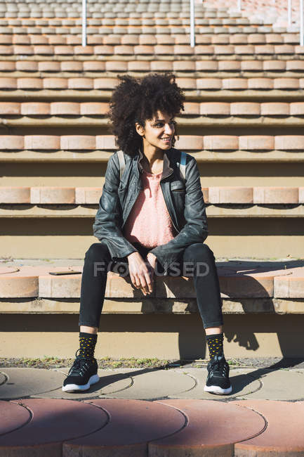 Black woman with afro hair sitting on the steps of a stadium — Stock Photo
