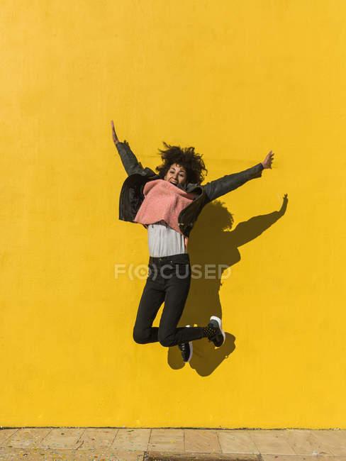 Femme noire avec des cheveux afro sautant de joie dans la rue avec un mur jaune en arrière-plan — Photo de stock