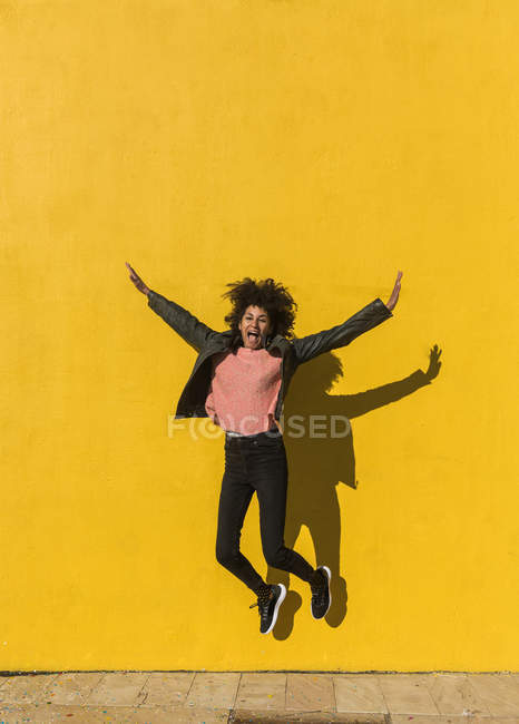 Black woman with afro hair jumping for joy in the street with a yellow wall in the background — Stock Photo