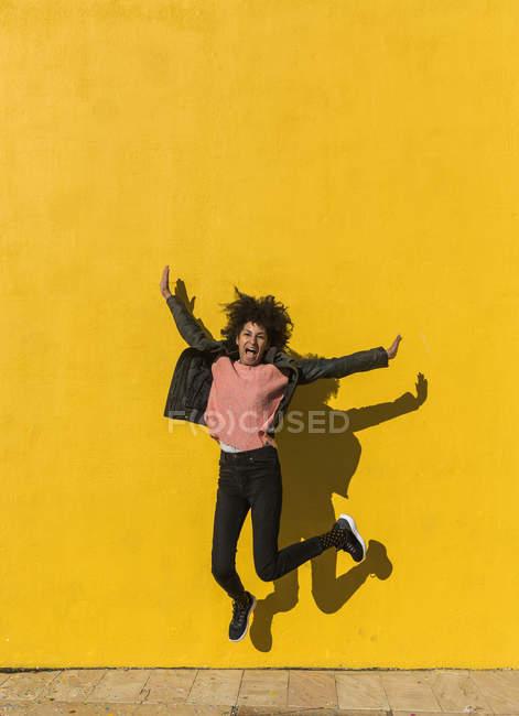 Donna nera con capelli afro che salta per la gioia in strada con un muro giallo sullo sfondo — Foto stock