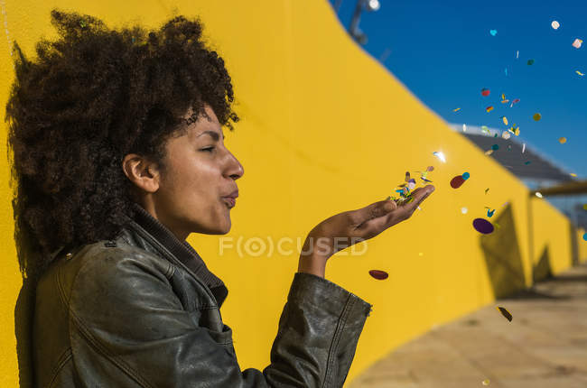 Black woman with afro hair throwing confetti to celebrate a very special day — Stock Photo
