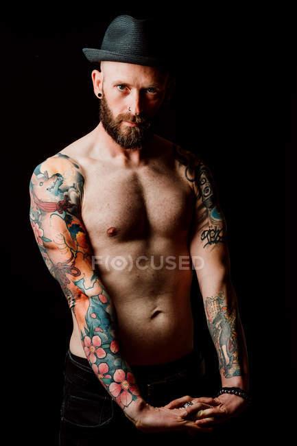 Desnudo calvo hipster serio con tatuajes en los brazos y sombrero mirando a la cámara sobre fondo negro - foto de stock