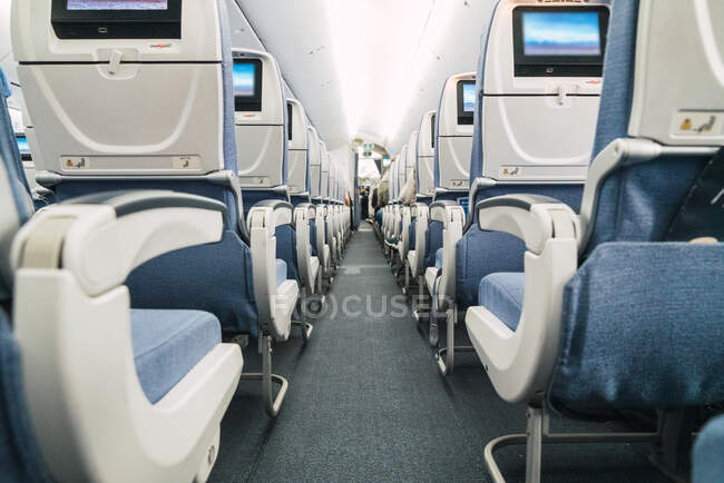 Narrow passage amidst comfortable seats inside modern aircraft cabin — Stock Photo