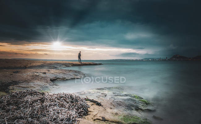Persona anónima pescando en lago tranquilo al amanecer - foto de stock