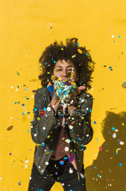 Чорна жінка з волоссям афро кидає конфетті, щоб відсвяткувати дуже особливий день. — стокове фото