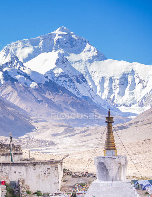 Shabby houses and temple near snowy mountain — Stock Photo