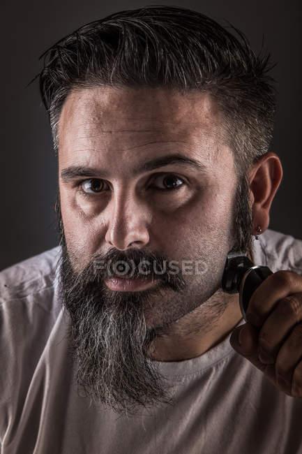 Бурштин голить бороду і дивиться на камеру. — стокове фото