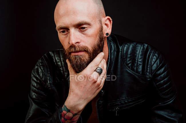 Задумчивый лысый хипстер в кожаной куртке с татуировками на руке, царапающий бороду на черном фоне — стоковое фото