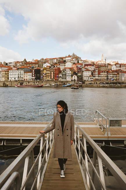 Bella donna in elegante elegante cappotto in piedi sul moderno molo vicino al fiume nella meravigliosa città invecchiata il giorno nuvoloso — Foto stock