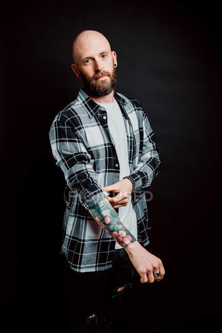 Bärtiger, haarloser Hipster im Hemd mit Tätowierungen an den Armen auf schwarzem Hintergrund — Stockfoto