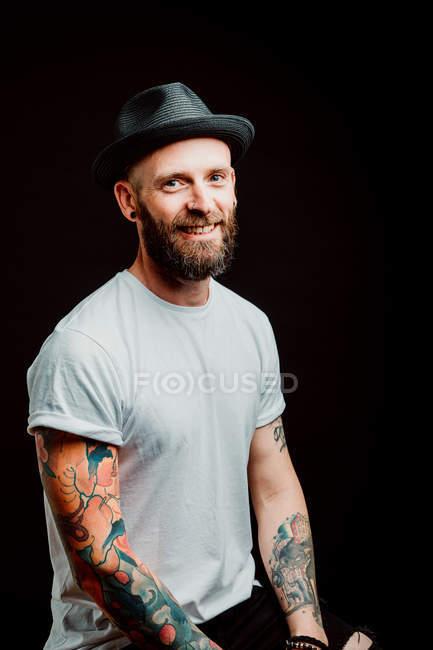 Веселий бородатий гіпстер у капелюсі і футболці з татуюваннями на руках на чорному тлі — стокове фото
