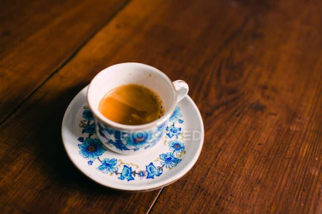 Маленькая чашка свежего горячего кофе на керамической тарелке на деревянном столе — стоковое фото