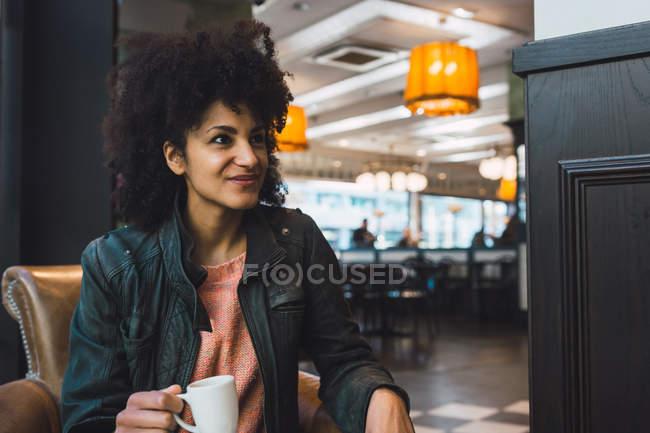 Mulher negra com cabelo afro bebendo um café em uma cafeteria — Fotografia de Stock