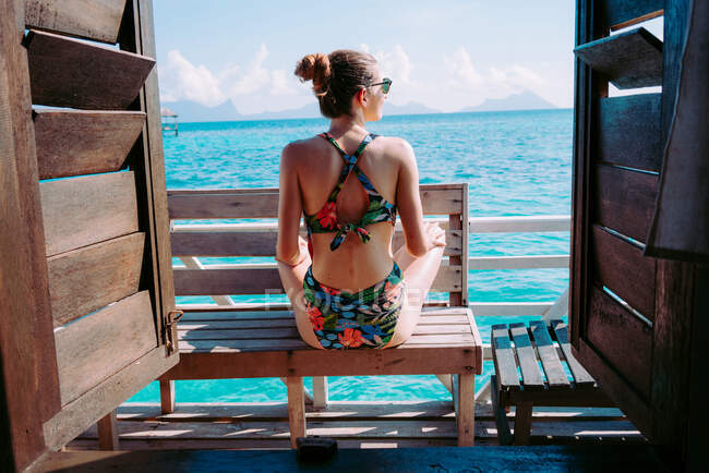 Back view of lady in swimsuit and sunglasses sitting on seat near blue sea in Jamaica — Stock Photo